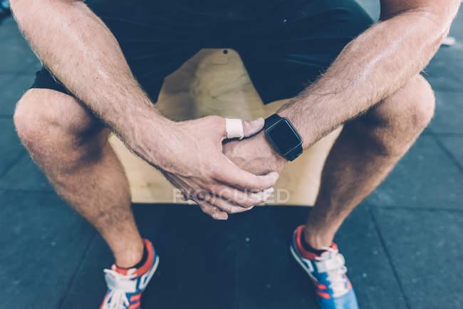 Tour de taille vers le bas de l'entraîneur masculin assis sur la boîte dans la salle de gym — Photo de stock