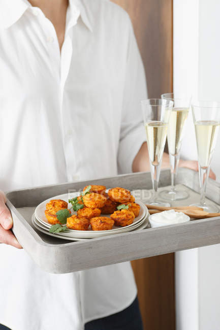 Man carrying tray of appetizers and champagne — Stock Photo