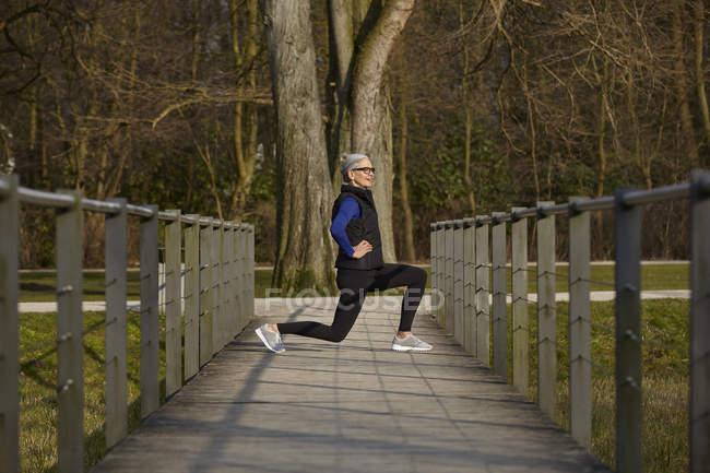 Longitud completa vista lateral de la mujer en el camino de madera, las manos en las caderas que se abalanzan - foto de stock