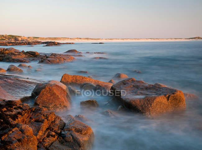 Vagues sur la plage de galets à vaisselle, exposition longue balle — Photo de stock