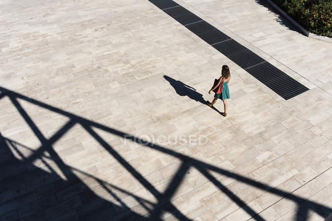 Vista de ángulo alto de la mujer con vestido de noche caminando por la plaza, Roma, Lazio, Italia - foto de stock