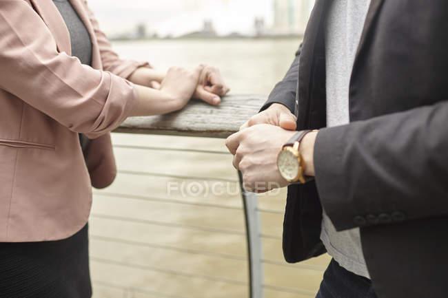 Section médiane de la femme d'affaires et homme d'affaires, réunion sur le front de mer, Londres, Royaume-Uni — Photo de stock