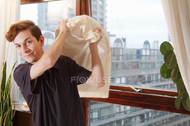 Людина холдингу подушку біля вікна — стокове фото