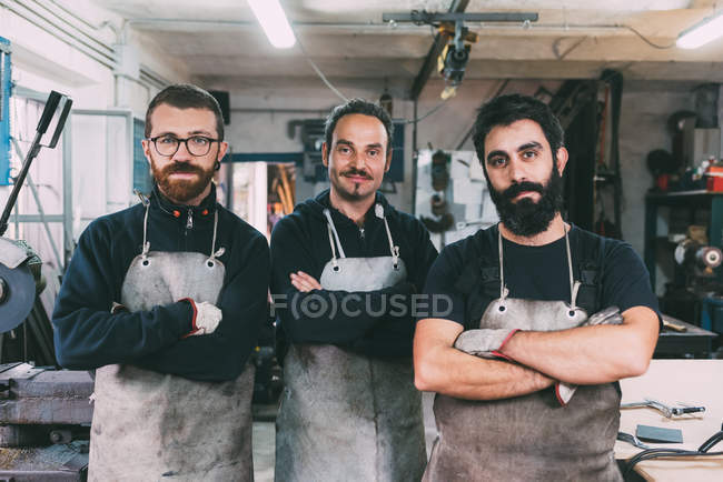 Portrait of three male metalworkers in forge workshop — Stock Photo