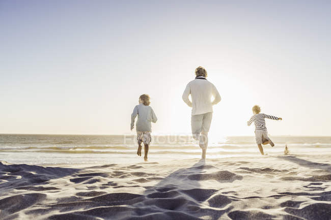 Rear view of father and children running on beach — Stock Photo