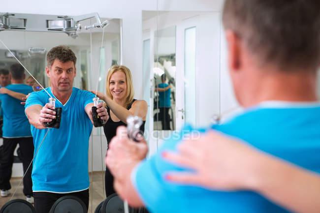 Тренер регулирует форму человека в тренажерном зале — стоковое фото