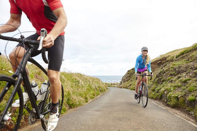 Ciclistas andando na estrada com vista para o oceano no dia ensolarado — Fotografia de Stock