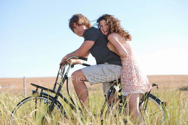 Пара їзда на велосипеді в високій траві — стокове фото