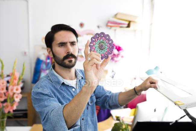 Jovem designer masculino segurando impressão circular no estúdio de impressão — Fotografia de Stock