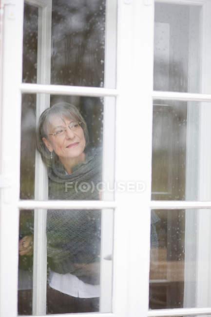 Alte Frau aus einem Fenster zu schauen — Stockfoto