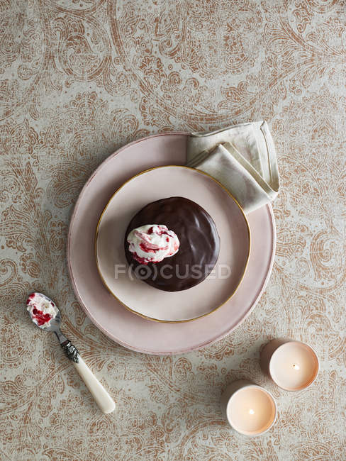 Chocolate cake with dollop of cream, top view — Stock Photo