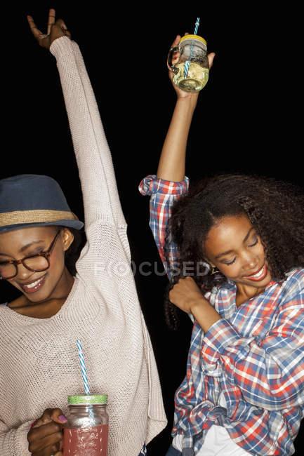 Jeunes femmes tenant des bocaux maçon bras levés regardant vers le bas souriant — Photo de stock