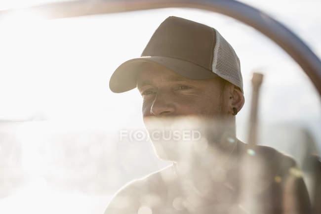 Porträt eines Mannes mit Baseballmütze auf einem Boot, der wegschaut — Stockfoto