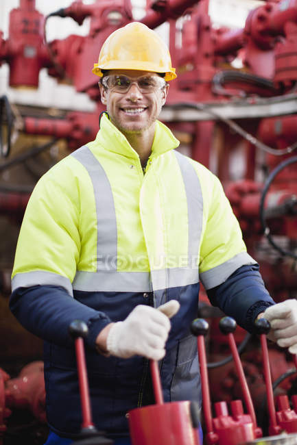 Worker operating machinery on oil rig — Stock Photo