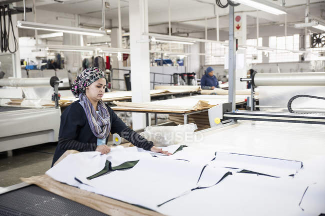 Trabalhador de fábrica removendo padrão têxtil cortado da máquina de corte padrão na fábrica de roupas — Fotografia de Stock