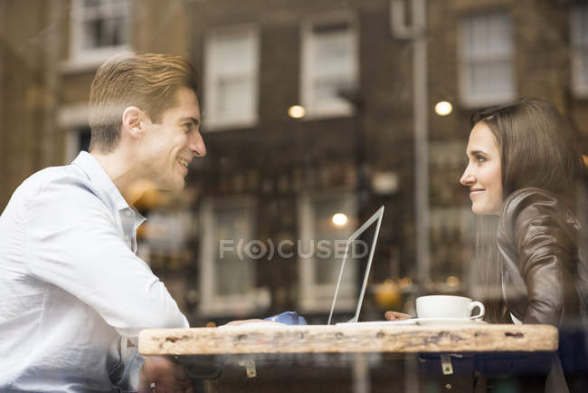 Young businessman and woman with laptop talking in cafe — Stock Photo