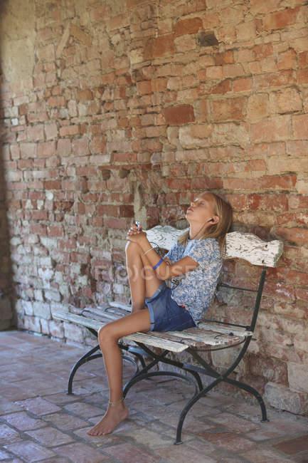 Девушка сидит на скамейке и слушает музыку в наушниках, Buonconvento, Тоскана, Италия — стоковое фото