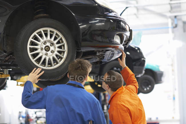 Rear view of college mechanic students inspecting  underneath of car — Stock Photo