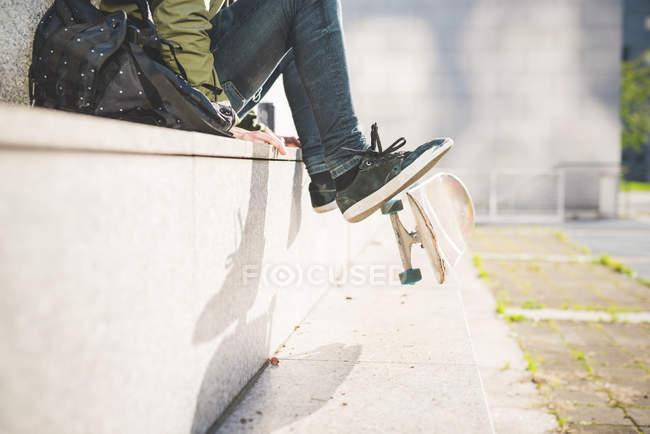 Vue de la taille vers le bas du jeune skate boarder urbain masculin assis sur le mur flipping skateboard avec les pieds — Photo de stock