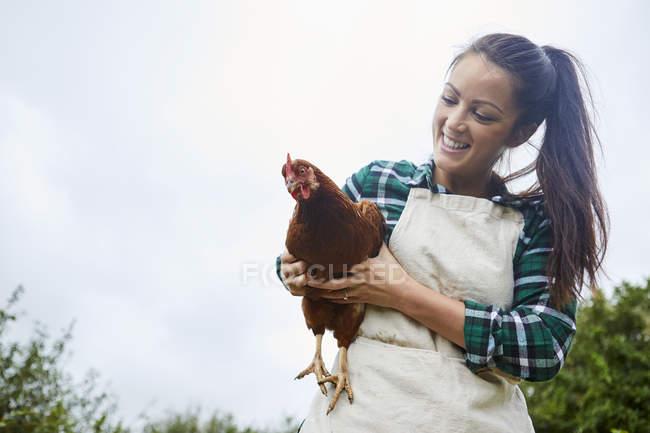 Mulher segurando frango nas mãos contra o céu azul — Fotografia de Stock