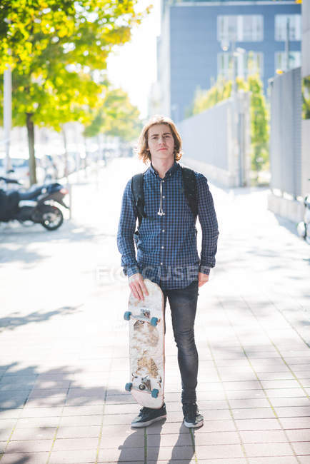 Portrait of confident young male urban skateboarder standing on sidewalk — Stock Photo