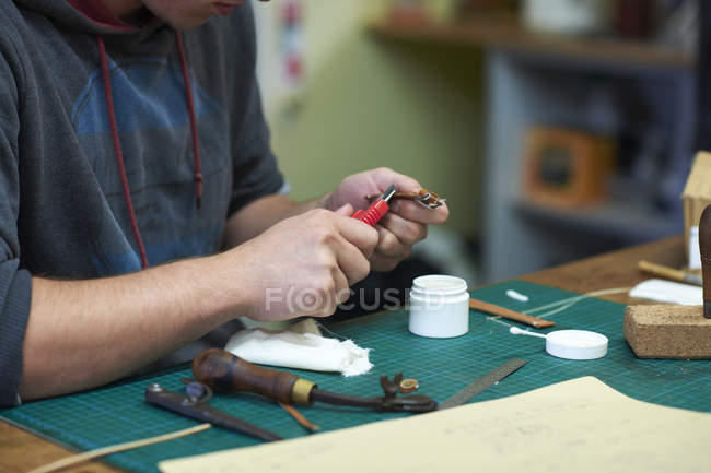 Male worker in leather workshop, making leather watch strap, mid section, close-up — Stock Photo