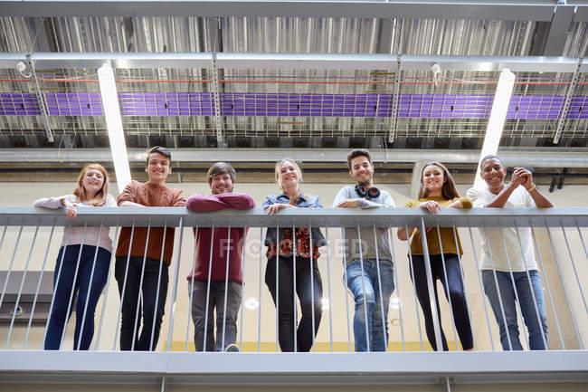 Portrait d'étudiants masculins et féminins regardant vers le bas depuis le balcon du collège d'enseignement supérieur — Photo de stock