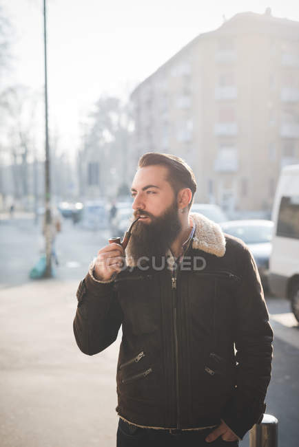 Young bearded man smoking pipe on street — Stock Photo