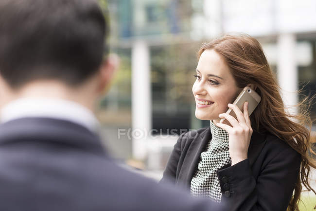 Businesswoman in city making telephone call — Stock Photo