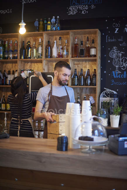 Baristas working behind counter in coffee shop — Stock Photo
