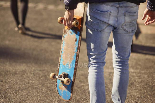 Jeune homme marchant en plein air, transportant skateboard, vue arrière, faible section, Bristol, Royaume-Uni — Photo de stock