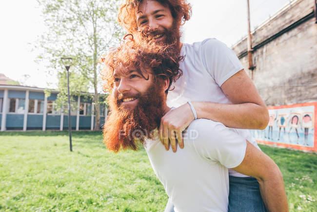 Jeune mâle hipster jumeaux avec barbe rouge dos piggy dans le parc — Photo de stock