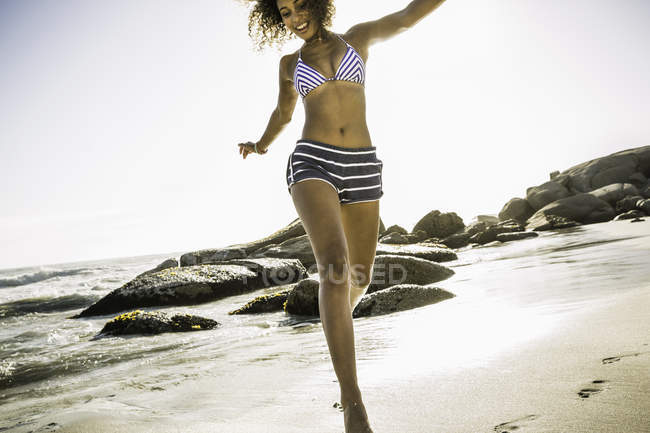 Woman jumping on beach — one person, south africa - Stock