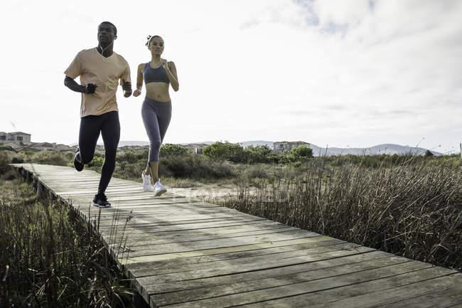 Couple jogging on wooden walkway — Stock Photo
