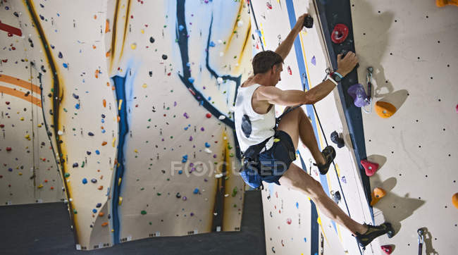 Зріла людина сходження з мотузок на скелелазіння стіна — стокове фото