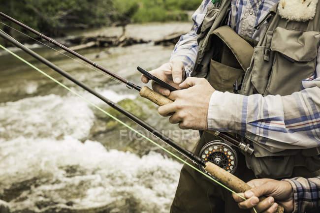 Recadrée vue du couple tenant des cannes à pêche et smartphone par rivière — Photo de stock