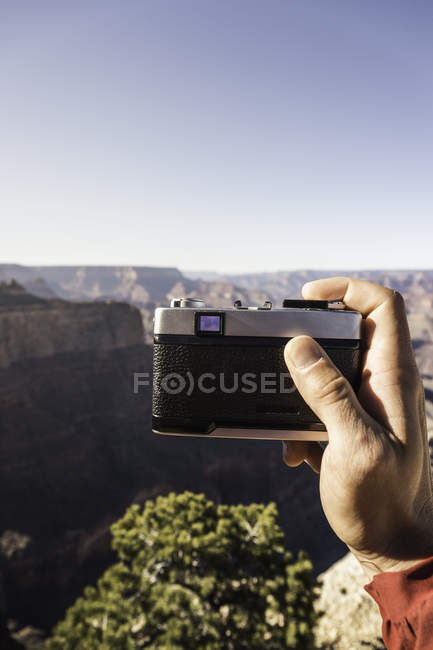 Male hand holding retro film camera with canyon landscape — Stock Photo