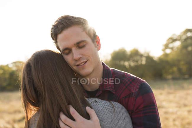 Junges Paar in ländlicher Umgebung, umarmt — Stockfoto