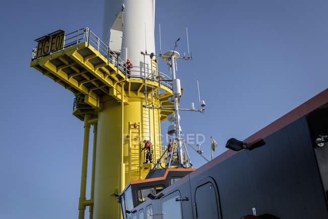 Ingegneri che scalano la turbina eolica dalla barca al parco eolico offshore — Foto stock