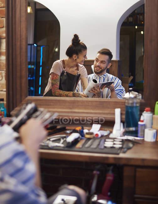 Image miroir de coiffeur montrant magazine client — Photo de stock