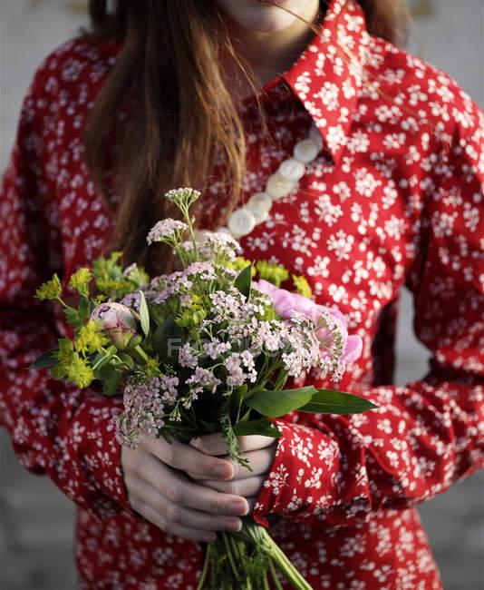 Куповані постріл жінка носить червоний квіткові блузка проведення букет квітів — стокове фото