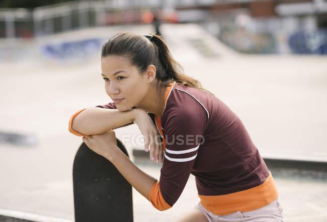 Weibliche Skateboarder im Skatepark stützte sich auf skateboard — Stockfoto