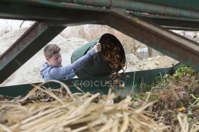 Adolescent vidange des déchets de jardin dans la poubelle de recyclage — Photo de stock