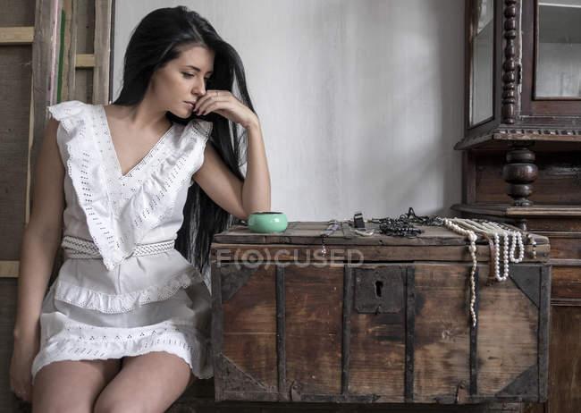 Giovane donna guardando gli accessori sul petto — Foto stock