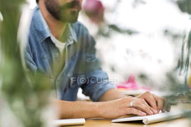 Cortada de tiro do designer masculino digitação em teclado em estúdio de impressão — Fotografia de Stock