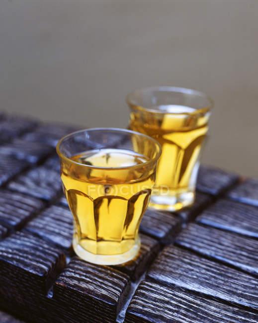 Пьет сидр в стаканах на деревянном столе — стоковое фото