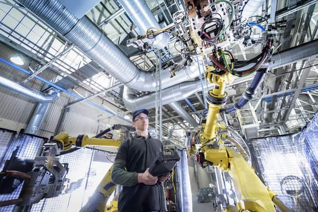 Apprentice engineer adjusting robot in car factory — Stock Photo