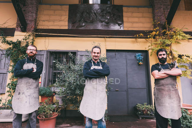 Portrait of three male metalworkers with arms folded outside forge — Stock Photo