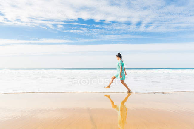 Молодая женщина, шагающая в океанские волны на пляже, Эль-Котильо, Фуэртевентура, Испания — стоковое фото
