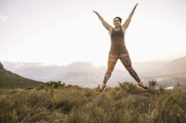 Femme de taille plus sur la montagne portant des vêtements de sport faisant saut en étoile en plein air — Photo de stock
